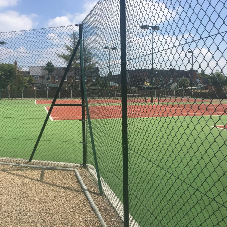 Chain link fence and posts around tennis courts